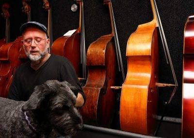 Luthier Jacco Stuitje in de winkel met hond